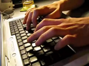Photo of hands typing on a laptop keyboard